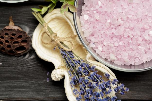 Composição aromática de lavanda, ervas, cosméticos e sal em um tampo de mesa escuro