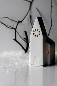 Composição atmosférica com casa de vela da igreja de cerâmica branca, flocos de neve, galho de árvore na parede branca.