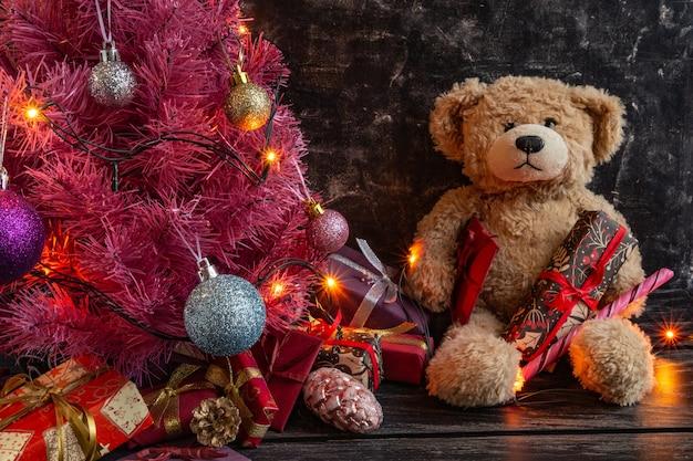 Composição atmosférica de natal ou ano novo árvore de natal rosa em fundo preto ursinho de pelúcia gif ...