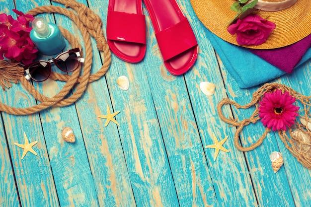 Composição brilhante de acessórios de praia feminina em fundo azul de madeira