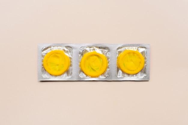Composição colorida com preservativos amarelos na superfície bege. sexo seguro e conceito anticoncepcional