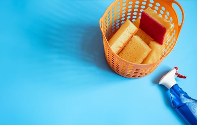 Composição colorida com um conjunto de esponjas de limpeza brilhantes e agente de limpeza. fundo de conceito de serviço de limpeza
