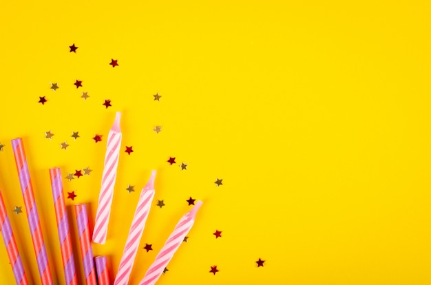 Composição colorida das palhas bebendo e dos balões de ar na decoração amarela do fundo, do partido e da celebração.