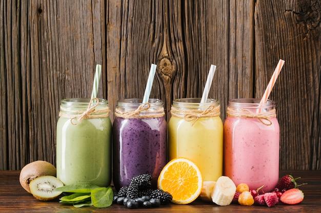 Composição colorida de frutas e smoothies em fundo de madeira