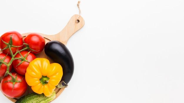 Composição colorida de vegetais na placa de madeira