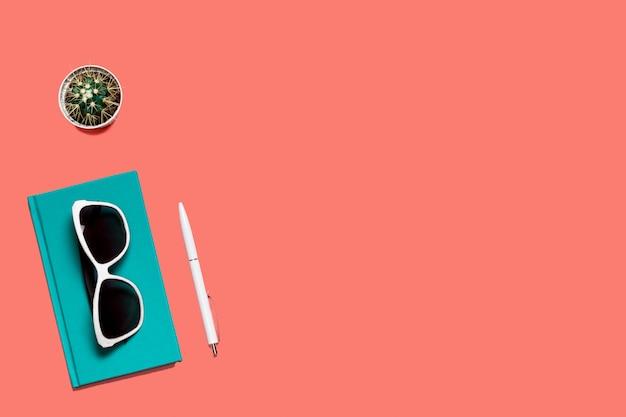 Composição colorida na moda plana leigos. mesa de cor coral com diário turquesa, óculos brancos, caneta e cacto.