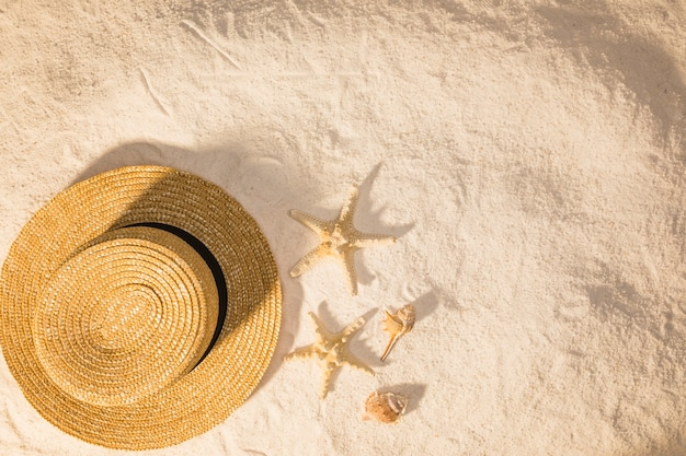 Composição com acessório de verão e estrela do mar na areia