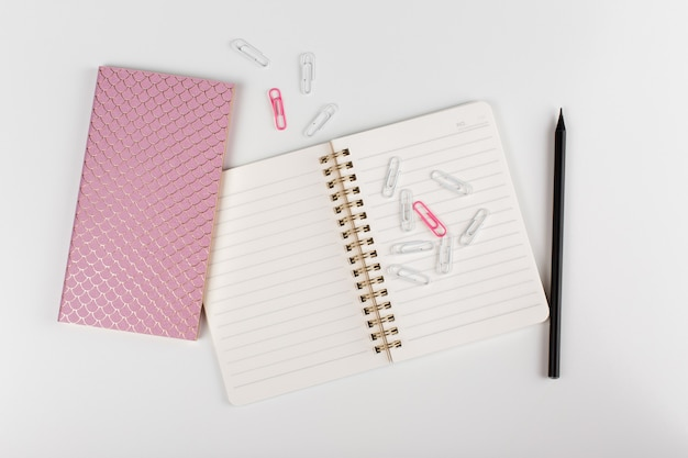 Composição com acessórios de negócios femininos. bloco de notas, lápis, clipes de papel no fundo branco. vista do topo. colocação plana.