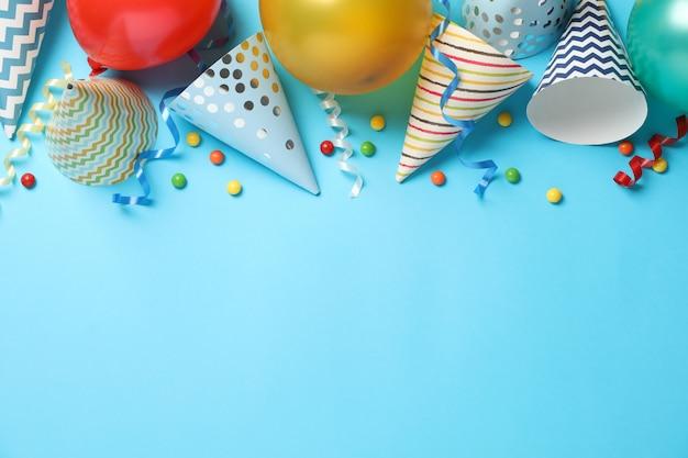 Composição com acessórios diferentes de aniversário em fundo azul, espaço para texto