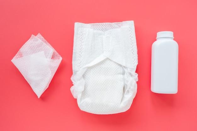 Composição com acessórios para bebês e cosméticos para creche em um fundo rosa