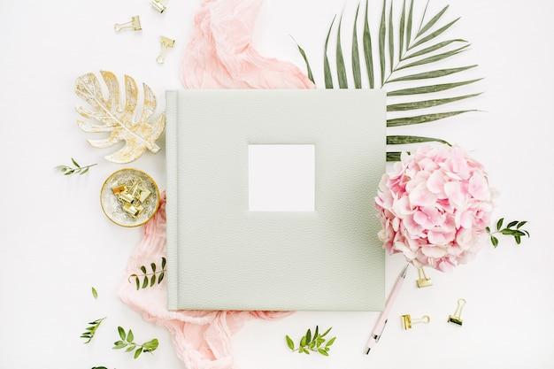 Composição com álbum de fotos de casamento ou família, buquê de flores de hortênsia, folha de palmeira tropical, cobertor rosa pastel, placa de ouro monstera na superfície branca