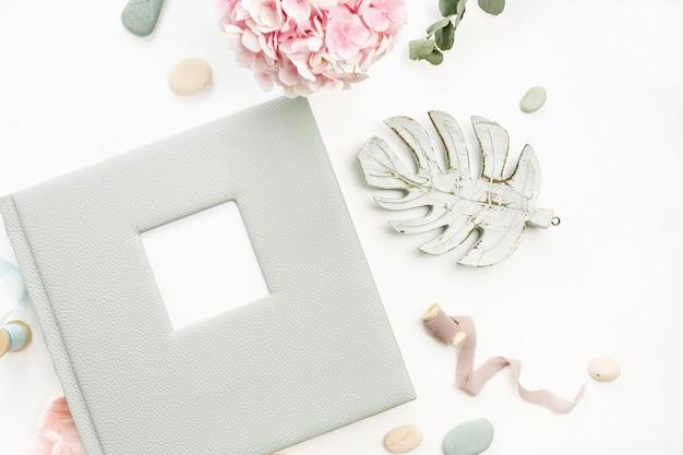 Composição com álbum de fotos de casamento ou família, buquê de flores de hortênsia, galho de eucalipto, cobertor rosa pastel, decoração de folha monstera na superfície branca