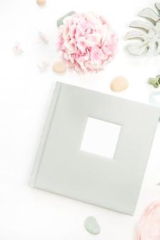 Composição com álbum de fotos de casamento ou família, buquê de flores de hortênsia rosa, placa de folhas de monstera na superfície branca