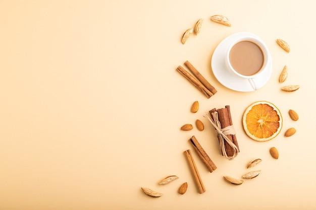 Composição com amêndoas, canela e café em fundo laranja pastel.