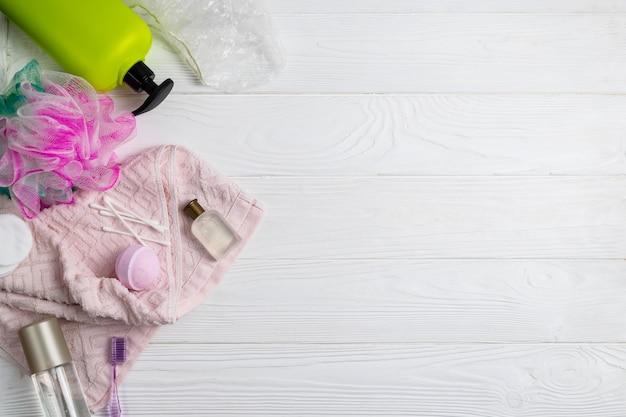 Composição, com, banho, acessórios, chuveiro, gel, toalha toalha washcloth, escova de dentes, branco, fundo madeira, com, copyspace