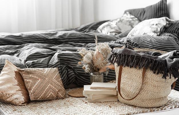 Composição com bolsa grande de palha de vime e elementos decorativos em um quarto.
