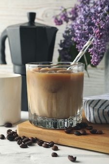 Composição com café gelado e flores em branco de madeira