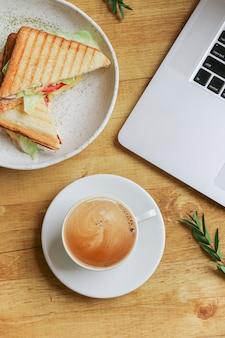 Composição com café, laptop, sanduíche e ramo de pistachi