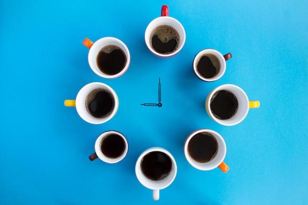 Composição com café preto em copos brilhantes e ponteiros do relógio no centro do fundo azul