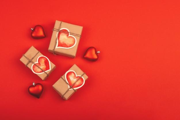 Composição com caixas de presente e corações de vidro em vermelho. fundo com espaço de cópia para o dia dos namorados.