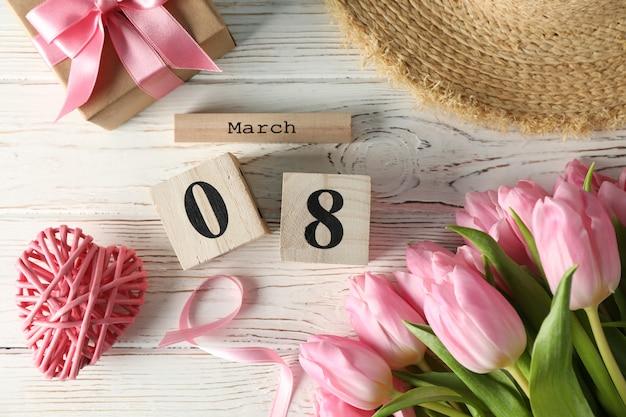 Composição com calendário de madeira e tulipas em fundo de madeira, vista superior