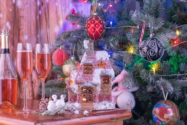 Composição com candelabros acesos, casa de papai noel e duas taças de champanhe.