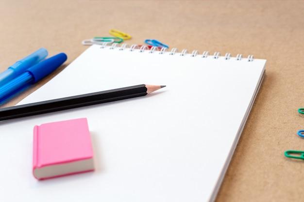 Composição com caneta colorida de caderno em branco, marcador e caneta