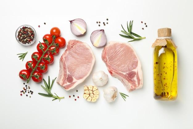 Composição com carne crua e ingredientes em fundo branco, vista superior