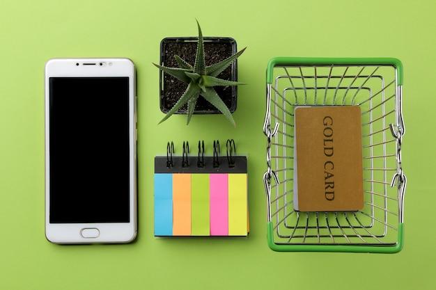 Composição com cartões de crédito, cacto em uma panela e um telefone em uma superfície verde