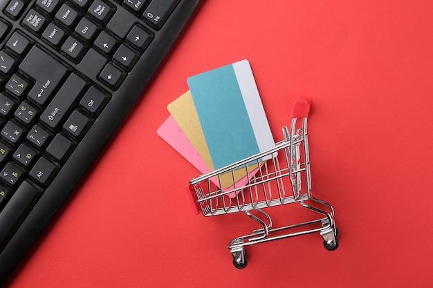 Composição com cartões de desconto e carrinho de compras em uma superfície vermelha