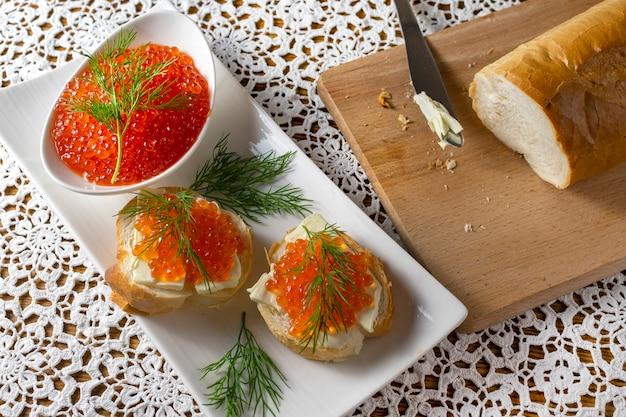 Composição com caviar vermelho no pão com manteiga, tigela branca com caviar vermelho e endro na mesa de madeira velha com toalha de mesa artesanal
