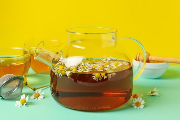 Composição com chá de camomila na mesa de hortelã contra amarelo