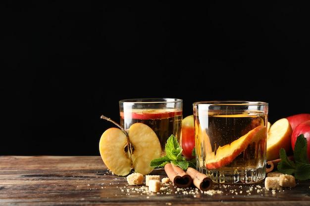 Composição com cidra, açúcar, canela e maçãs na mesa de madeira