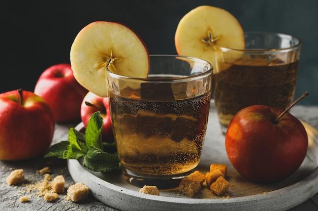 Composição com cidra, açúcar e maçãs na mesa cinza