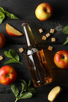 Composição com cidra, açúcar e maçãs na mesa de madeira