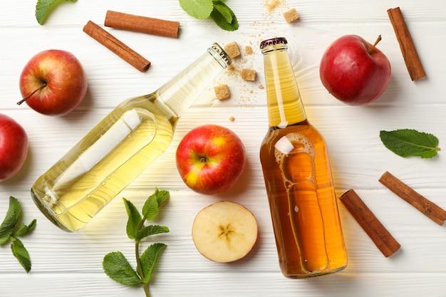 Composição com cidra, canela e maçãs na mesa de madeira branca