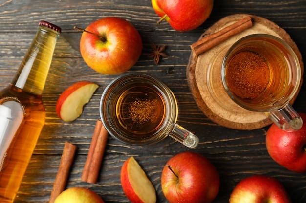 Composição com cidra, canela e maçãs na mesa de madeira