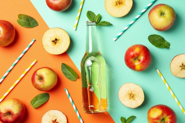 Composição com cidra, maçãs e canudos em dois tons