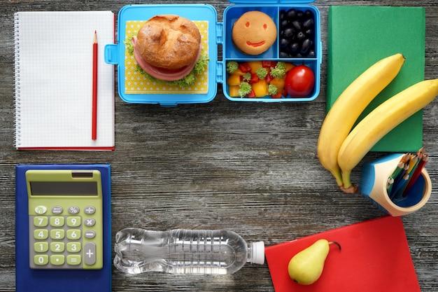 Composição com comida apetitosa para o aluno e papelaria na mesa de madeira