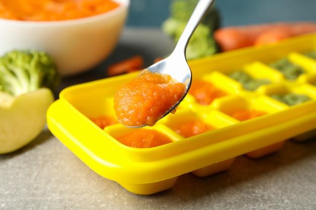 Composição com comida para bebé no fundo cinzento, close-up