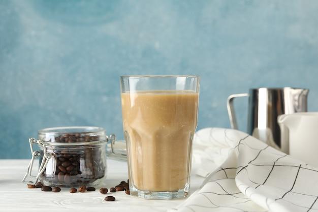 Composição com copo de café gelado na mesa de madeira branca