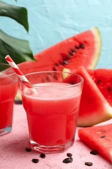 Composição com copo de suco de melancia e fatias na mesa-de-rosa