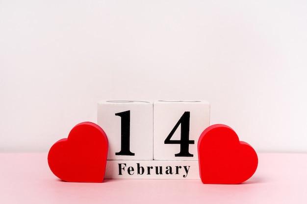 Composição com corações para fevereiro em um fundo rosa com um calendário de madeira