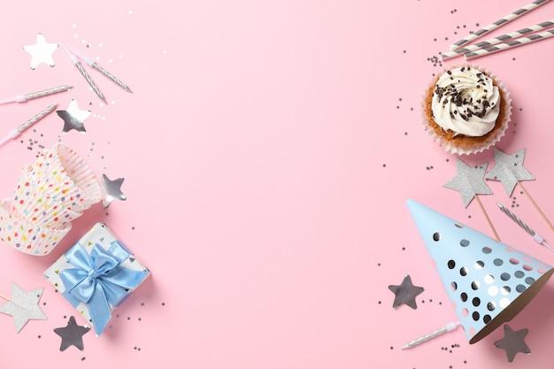 Composição com cupcake e aniversário acessórios em fundo rosa, espaço para texto