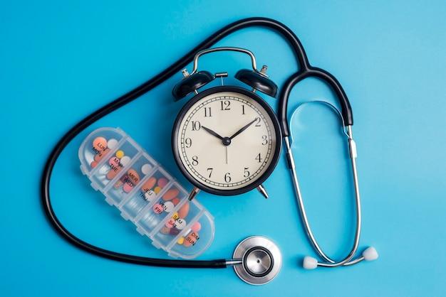 Composição com despertador de estetoscópio médico e comprimidos em um azul
