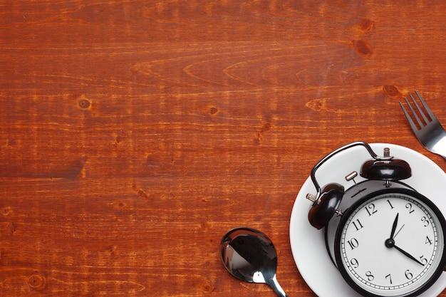 Composição com despertador, prato e utensílios