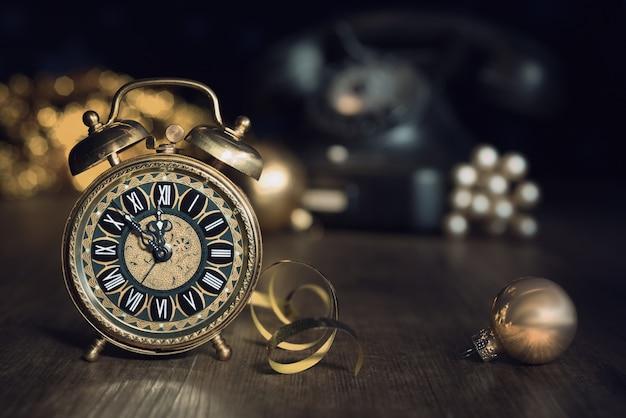 Composição com despertador vintage mostrando cinco a meia-noite