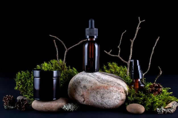 Composição com diversos frascos de vidro de cuidado corporal em pedestal de pedra com musgos