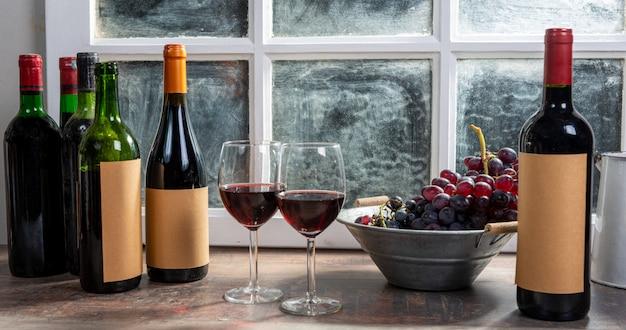Composição com dois copos de vinho, uvas e garrafas de vinho tinto