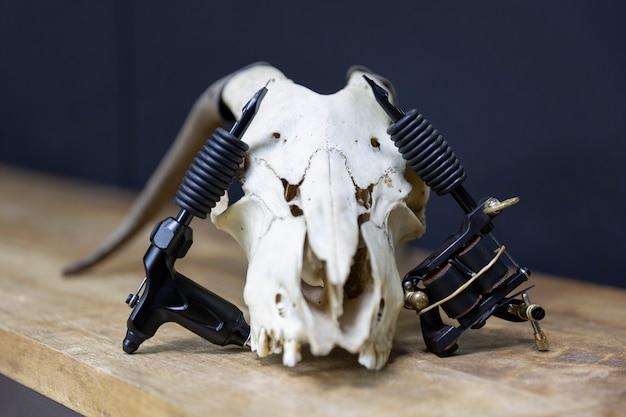 Composição com dois modelos diferentes de máquinas de tatuagem repousando sobre um crânio de cabra em um estúdio de tatuagem.
